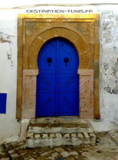 Une porte typique : cloutée, bleue, avec son encadrement en grès sculpté